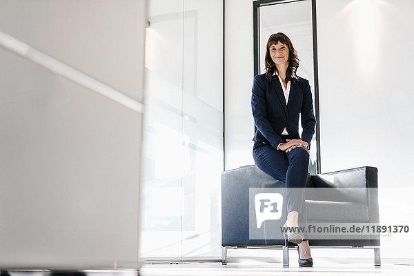 Erfolgreiche Geschäftsfrau auf dem Sessel sitzend