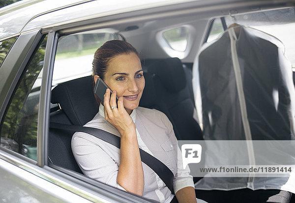 Geschäftsfrau am Telefon sitzend auf dem Rücksitz eines Autos