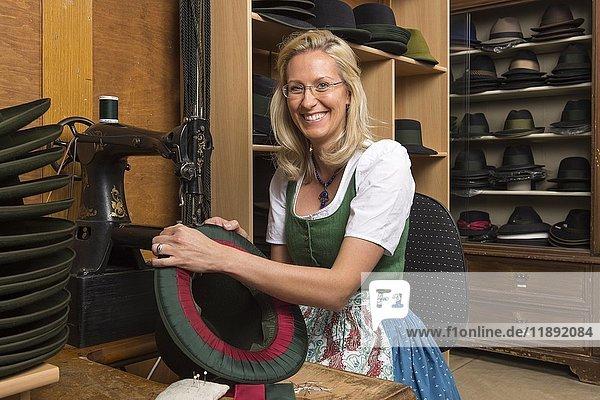 Frau näht Seidenband und Unterrandfutter auf Hutrand  hinten fertige Hüte in Regal  Hutmacher  Bad Aussee  Steiermark  Österreich  Europa