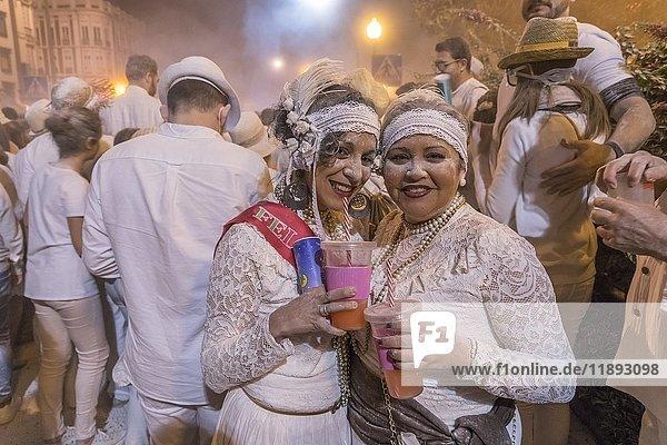 Two woman posing in front of crowd  white powder and white clothes  carnival La fiesta de los Indianos  Las Palmas de Gran Canaria  Canary Islands  Spain  Europe