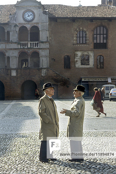 Elderly people talking in Piazza della Vittoria  Pavia - Italy