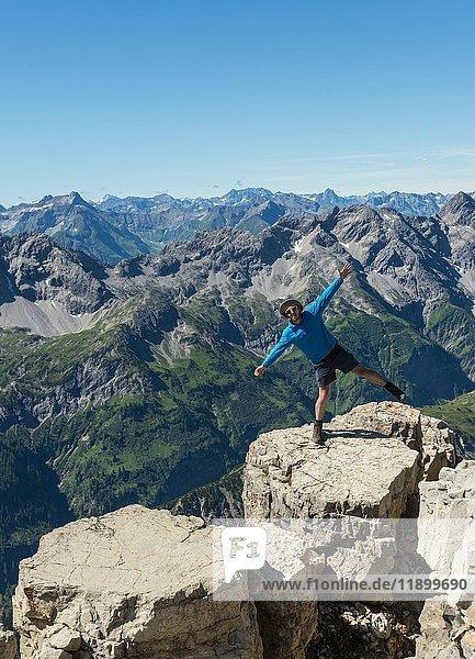 Wanderer steht auf einem Bein  Berge und Alpen  Gipfel des Hochvogel  Allgäu  Allgäuer Hochalpen  Bayern  Deutschland  Europa