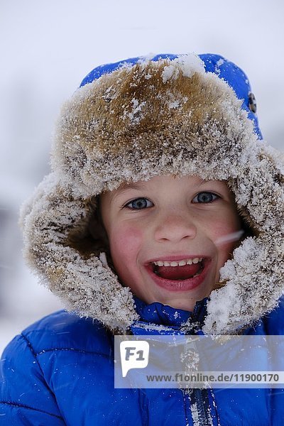 Laughing child  portrait with fur hat in snow  Germany  Europe