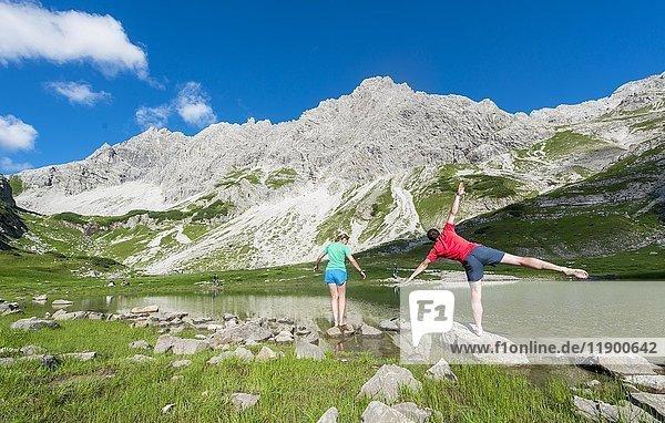 Wander stehen auf Steinen und turnen  Bergsee beim Printz-Luitpolt-Haus  Allgäuer Alpen  Bad Hindelang  Allgäu  Bayern  Deutschland  Europa