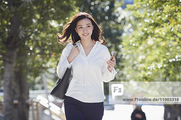 Japanese woman walking in city park in Tokyo