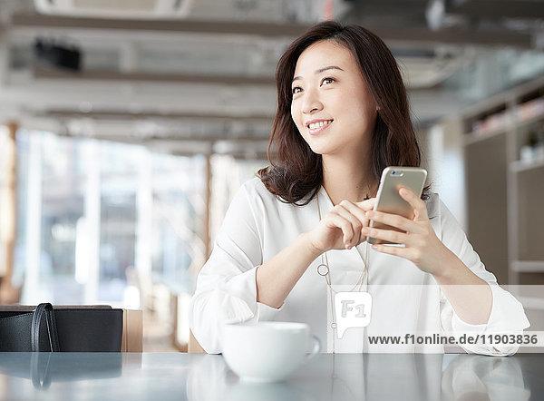 Japanische Frau mit Smartphone in einem schicken Cafe