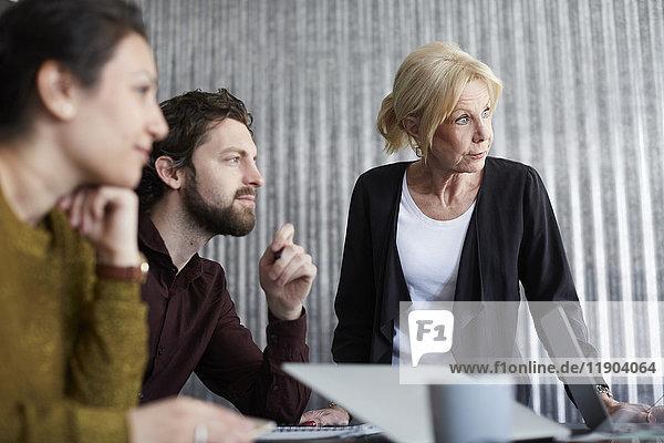 Senior Geschäftsfrau mit mittelgroßen Kollegen  die im Vorstandszimmer wegschauen