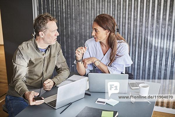 Reife Geschäftskollegen diskutieren im Sitzen mit dem Laptop am Konferenztisch im Sitzungssaal