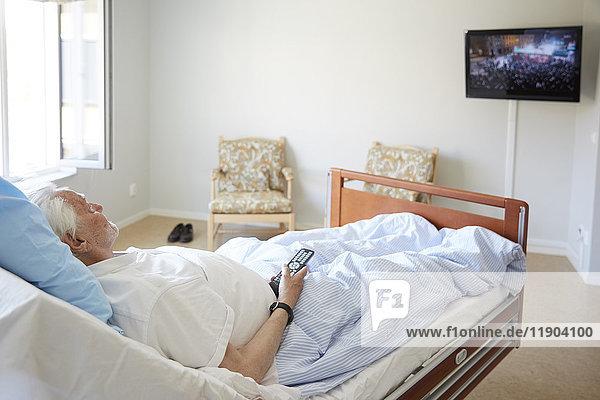 Älterer Mann beim Fernsehen auf dem Bett in der Krankenstation