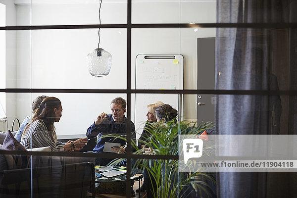 Business-Team im Sitzungssaal während der Besprechung aus Glas im Büro gesehen