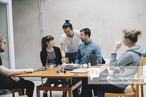 Multiethnische Programmierer  die am Schreibtisch im Büro arbeiten