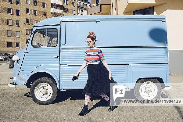 Junge Frau  die mit einem blauen Minivan auf der Straße unterwegs ist.