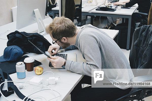 Seitenansicht des Computerprogrammierers beim Befestigen des digitalen Tabletts an der Tastatur am Schreibtisch im Büro Seitenansicht des Computerprogrammierers beim Befestigen des digitalen Tabletts an der Tastatur am Schreibtisch im Büro
