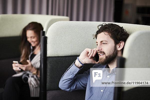Lächelnde Geschäftskollegen mit Smartphones auf Stühlen im Kreativbüro