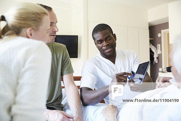 Krankenpfleger diskutiert über digitale Tablette mit dem Paar  während der ältere Mann auf dem Krankenhausbett liegt.