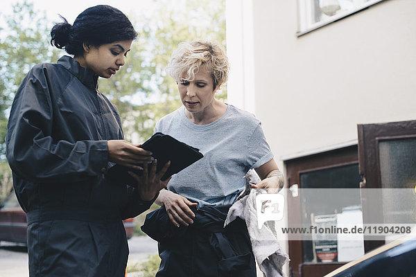 Mechanikerin erklärt den Kunden über das digitale Tablett außerhalb der Werkstatt