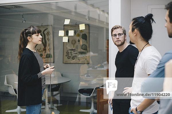 Programmiererinnen und Programmierer diskutieren über Haftnotizen  die im Büro auf Glas geklebt werden.