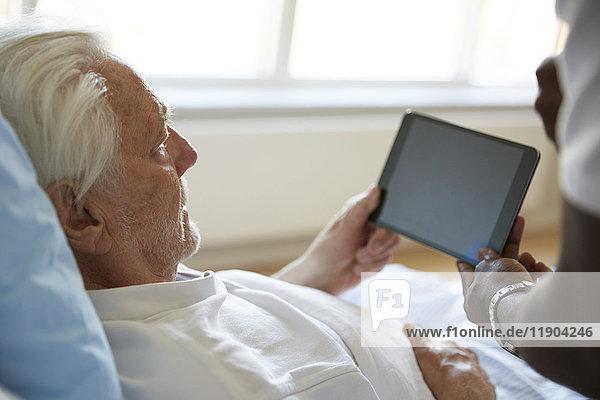 Abgeschnittenes Bild eines Krankenpflegers  der den älteren Mann bei der Verwendung von digitalen Tabletten im Krankenhaus unterstützt.