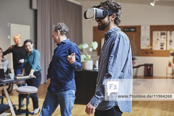 Geschäftsmann nutzt Virtual-Reality-Simulator  während er Kollegen im Kreativbüro zur Seite steht.