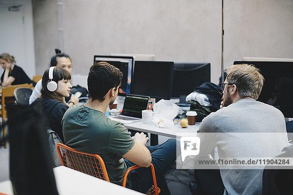 Computerprogrammierer diskutieren am Schreibtisch im Büro