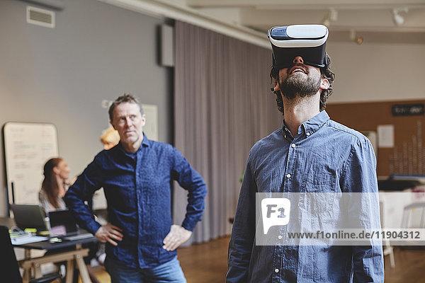 Der reife Geschäftsmann steht mit den Händen auf der Hüfte  während er den männlichen Kollegen mit Hilfe des Virtual-Reality-Simulators in kreativen