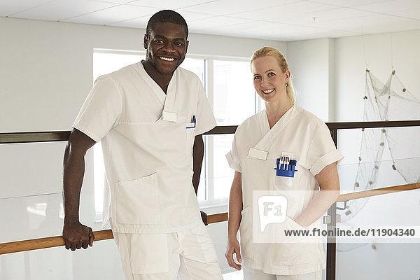 Porträt von selbstbewussten Krankenschwestern und Krankenpflegern  die am Geländer im Krankenhausflur stehen.