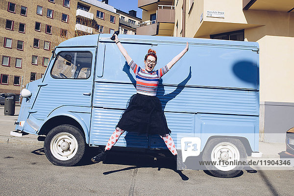 Volle Länge der jungen Frau  die gegen einen blauen Minivan auf der Stadtstraße springt.