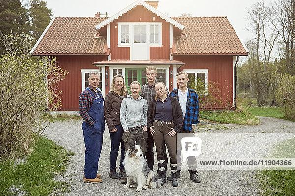 Porträt einer lächelnden Familie mit einem Australian Shepherd auf einem Wanderweg.