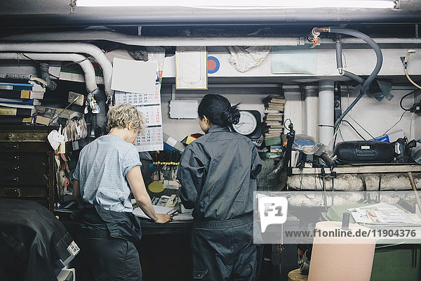 Rear view of female coworkers standing by workbench at auto repair shop