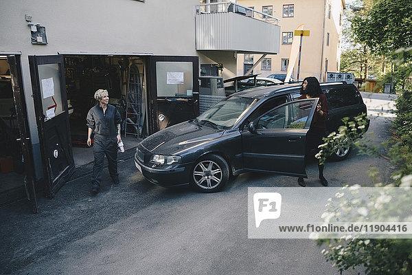 Mechanikerin beim Kunden beim Öffnen der Autotür vor der Autowerkstatt