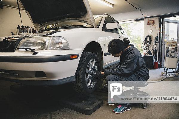 Seitenansicht der Mechanikerin  die das Autorad in der Autowerkstatt untersucht.