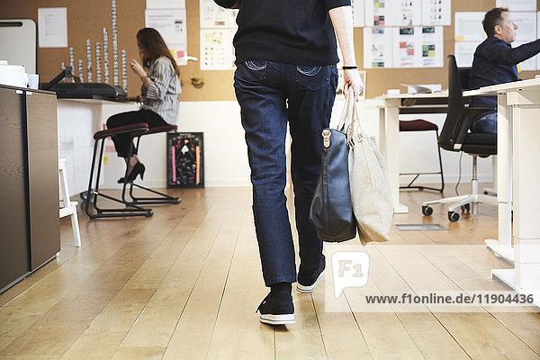 Rückansicht der Seniorin mit Geldbörse und Tasche inmitten von Kollegen im Kreativbüro