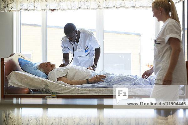 Krankenschwester schaut auf männlichen Kollegen  der den älteren Mann auf der Krankenstation untersucht.