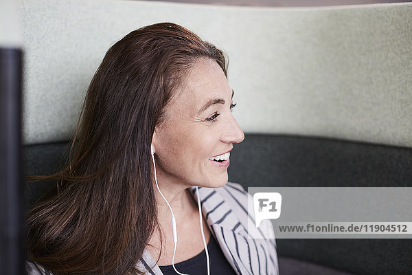 Smiling mature businesswoman with headphones sitting on chair at creative office