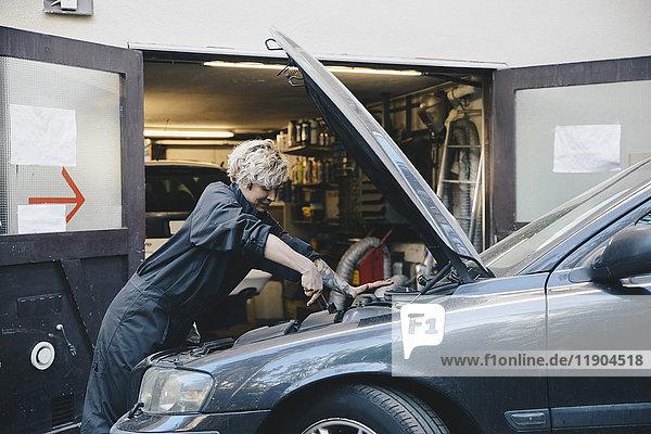 Seitenansicht eines weiblichen Mechanikers außerhalb der Autowerkstatt