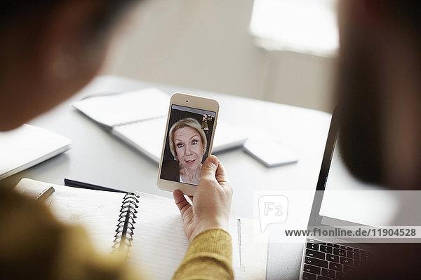 Kollegen-Videokonferenz mit Senior-Geschäftsfrau auf Smartphone im Vorstandszimmer