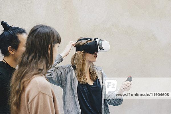 Computerprogrammierer mit Fernsteuerung beim Tragen einer VR-Brille durch Kollegen im Büro
