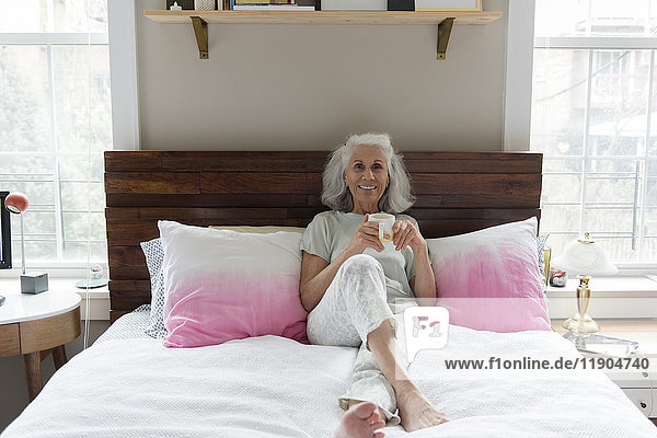 Smiling older woman drinking coffee in bed