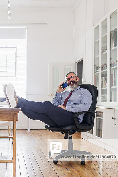Caucasian man with feet up talking on cell phone