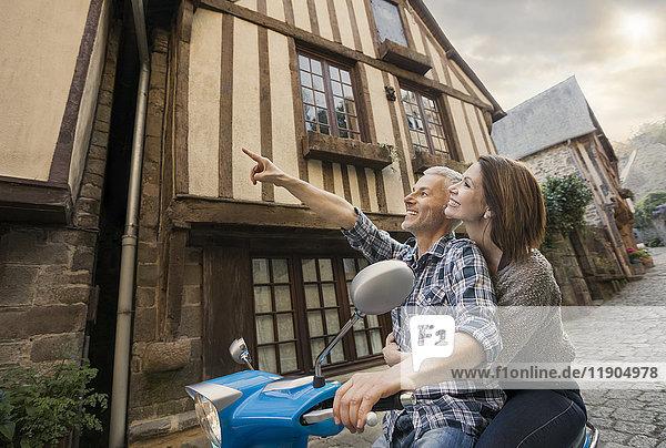 Caucasian couple sightseeing on motor scooter