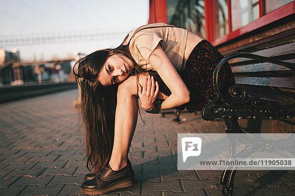 Caucasian woman sitting on bench holding legs