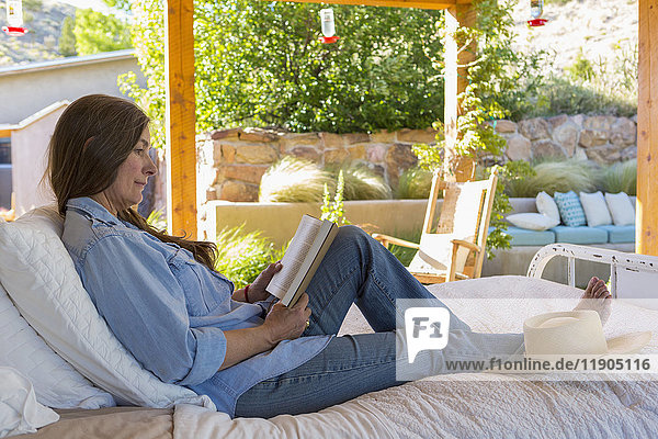 Older Caucasian woman laying on bed reading book in garden