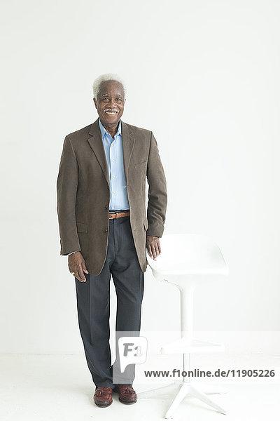 Portrait of older Black man leaning on store