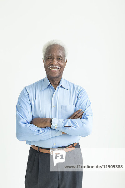 Portrait of smiling older Black man with arms crossed