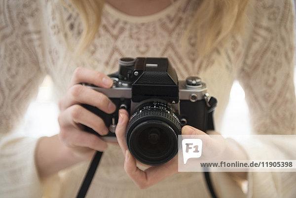 Hands of Caucasian woman focusing lens on camera