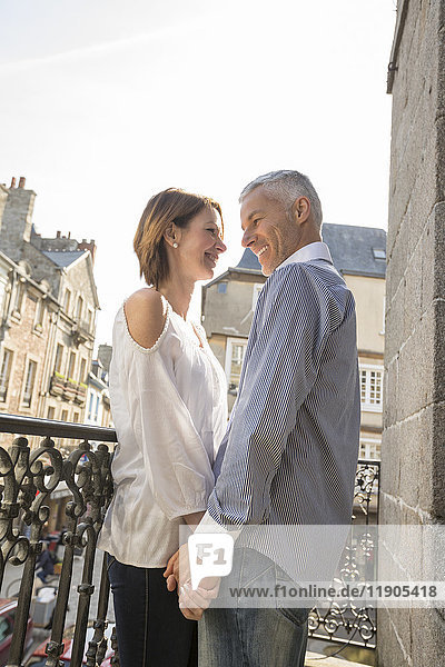 Caucasian couple holding hands on balcony in city