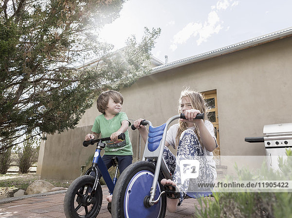 Caucasian boy and girl riding bicycles near house