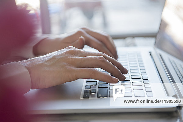 Hands of Caucasian woman typing on laptop