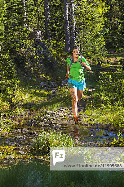 Hispanic woman running on wet trail