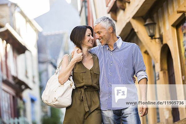 Caucasian couple hugging in the city